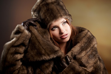 Attractive woman in brown  fur coat with hood