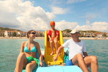 family with girl on pedal boat with yellow slide in sea