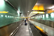 people go into long, green corridor for boarding at airplane