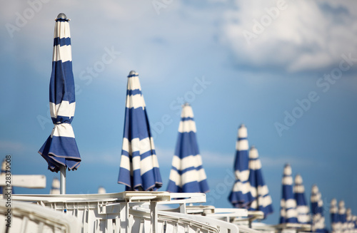 many white loungers and blue beach umbrellas on sand at beach