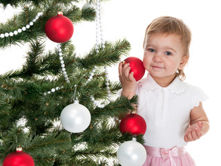 Toddler decorating christmas tree with red and white balls