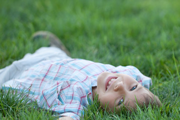 Kid lying in the green grass