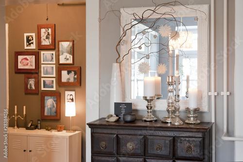 Kommode mit Kerzen vor Bilderrahmen