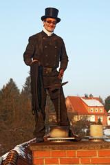 chimney sweep with stovepipe hat working upon the roof 02