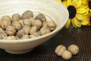wooden bowl with walnuts on mat