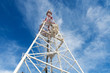 Telecommunication tower with antennas against blue sky backgroun