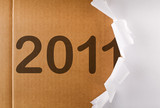 Torn wrapping paper revealing cardboard box - new year concept poster