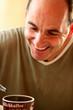 Mann lachend über einer Kaffeetasse