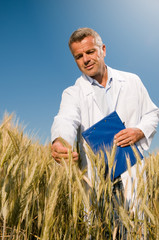 Smiling technician controls wheat field