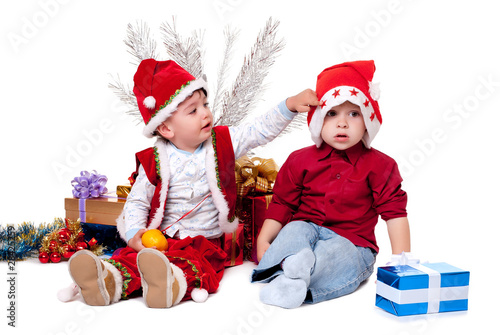 Two kids in Santa hats beside Christmas tree