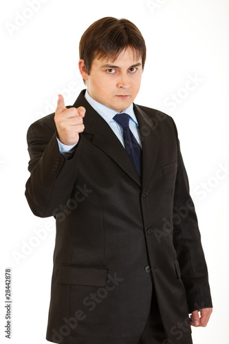 Strict young  businessman shaking his finger isolated on white.