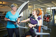 Fitnesstrainer redet mit Frau