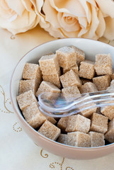 Bowl with brown sugar cubes and spoons