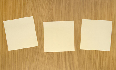 Three yellow sticky notes on wooden door