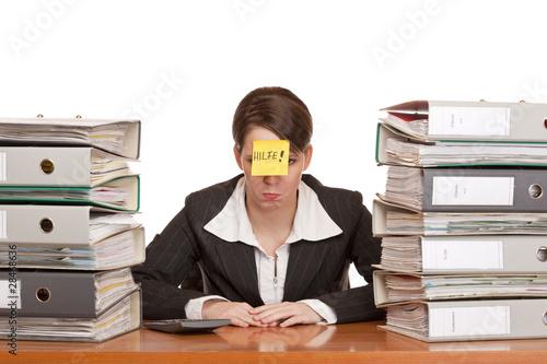 Überlastete Frau im Büro zwischen Ordnerstapeln benötigt Hilfe