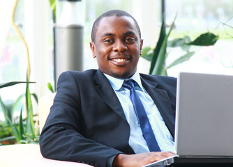a handsome young business man with a laptop