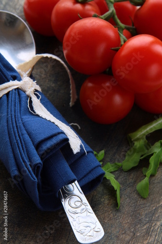 Fresh cherry tomato with spoon on table