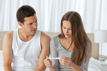 Worried couple looking at a pregnancy test sitting on their bed