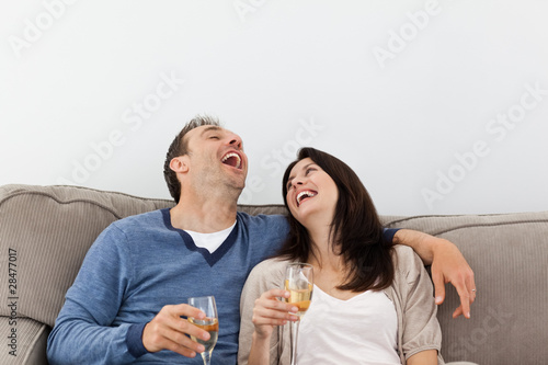 Couple laughing while drinking champagne on the sofa