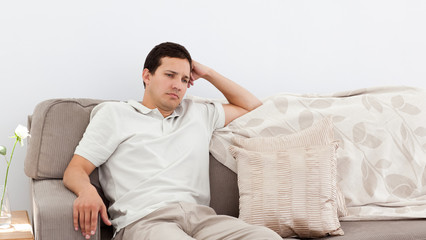 Depressed man thinking on the sofa