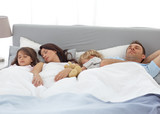 Tranquil children sleeping with their parents