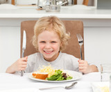 Fototapety Excited boy holding forks to eat pasta and salad