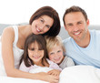 canvas print picture - Lovely family sitting together on the bed
