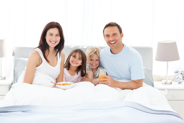 Happy family having breakfast together on the bed