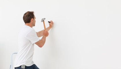 Rear view of a man hammering against a white wall
