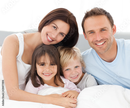 Lovely family sitting together on the bed