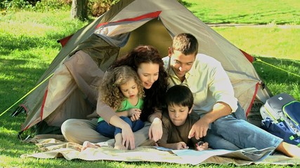 Family looking at a map siiting in front of a tent