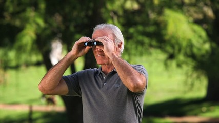 Old man using binoculars