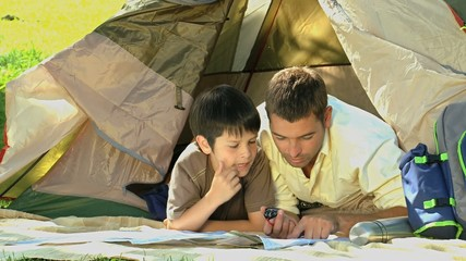 Father and son looking at a map lying in a tent