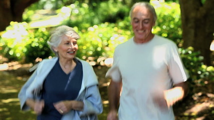 Elderly couple taking a break after running