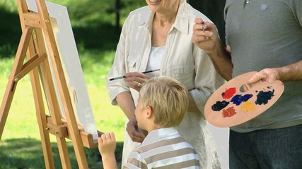 Boy and grandparents painting a canvas