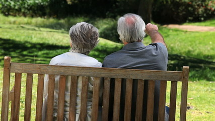 Elderly couple looking at something sitting on a bench