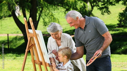 Young boy painting a canvas with grandparents