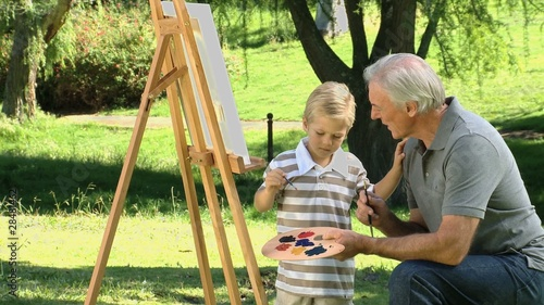 Young child painting a canvas with grandfather