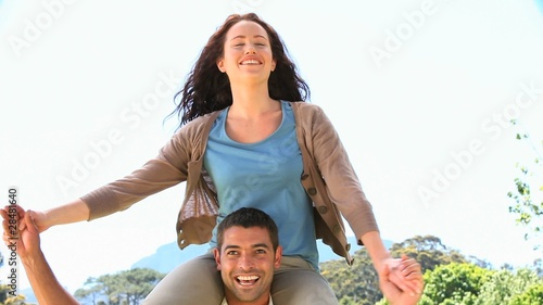 Smiling woman on the shoulders of her husband