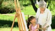 Young girl painting a canvas with grandmother