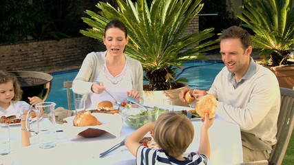 Cute family having lunch in the garden