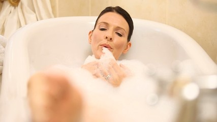 Happy woman relaxing in the bathtub