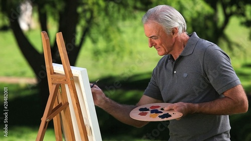 Old man painting a canvas