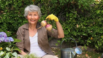 Old woman gardening and smiling at the camera