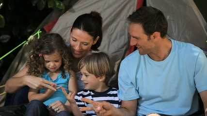 Family palying in front of a tent
