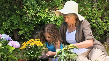 Old woman and her granddaughter gardening together