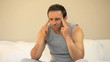 Man having a headache sitting on the bed