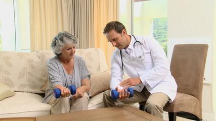 Young doctor showing to a old woman the use of dumbbells