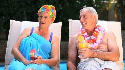 Old couple relaxing near the pool.