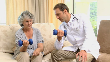 Young doctor showing to his old patient the use of dumbbells
